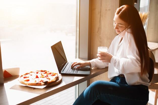 Женская модель работает на ноутбуке и говорит по телефону.