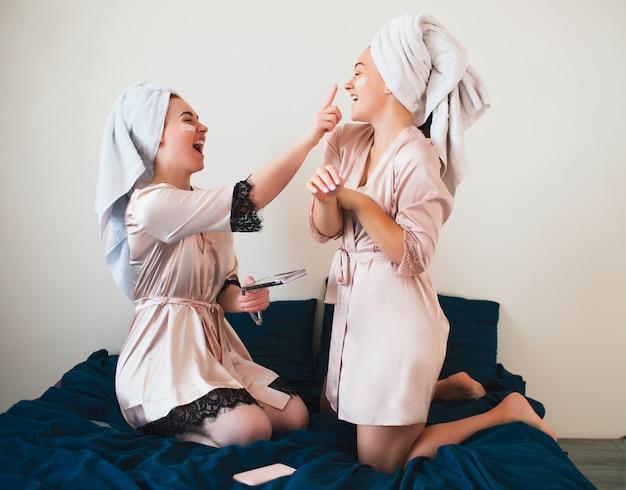 여성 모델은 얼굴에 크림을 바르십시오. 수건과 잠옷을 입은 두 명의 젊은 여성은 가정에서 함께 즐거운 스파 파티를 즐깁니다.