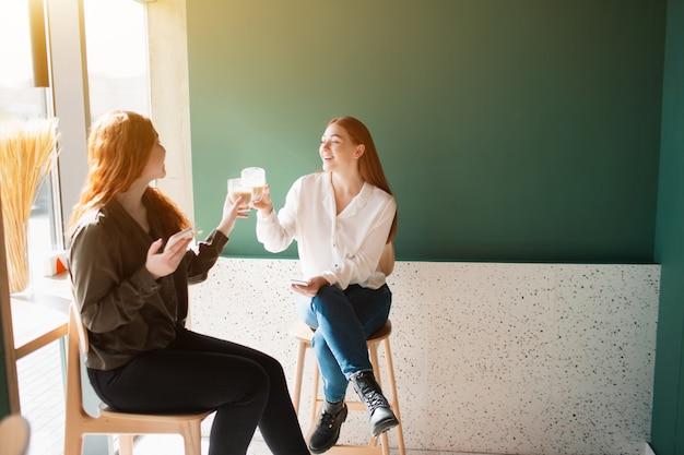 Женские модели пьют кофе в кафе. молодые женщины говорят и улыбаются