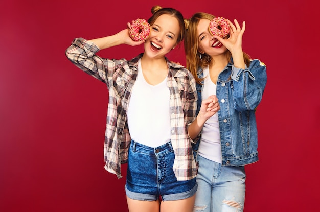 Female models holding pink donuts with sprinkles