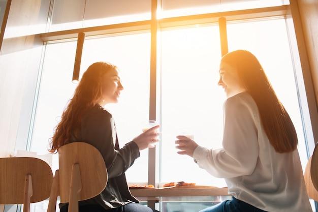 女性モデルが座ってカフェで話します。昼食時にコーヒーを飲んでいる若い女性