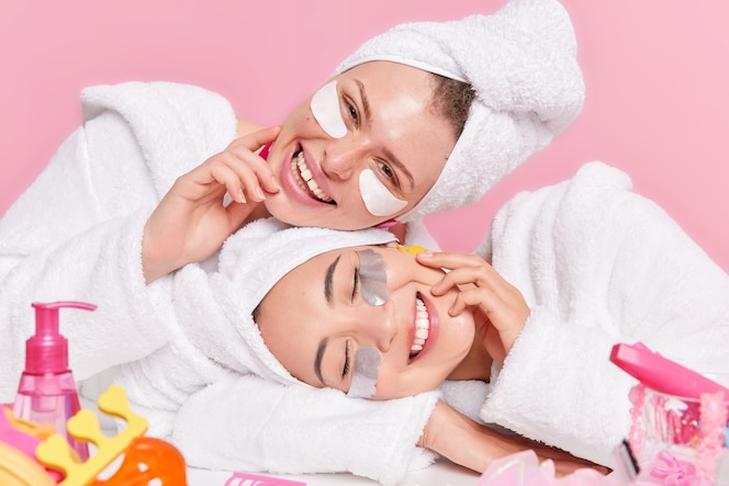 Female models smile gladfully tilt heads apply beauty patches under eyes enjoys skin care procedures dressed in white soft bathrobes isolated on pink