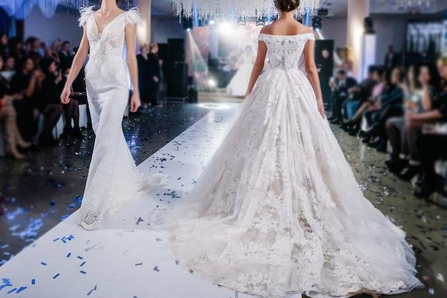 Девушки-модели выходят на подиум в красивых стильных белых свадебных платьях во время показа мод