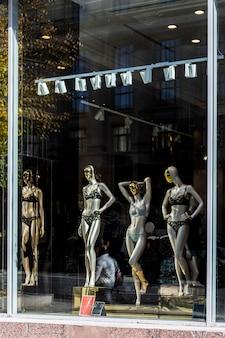 通りの反射とショーウィンドウでポーズをとる下着の女性のモダンなマネキン