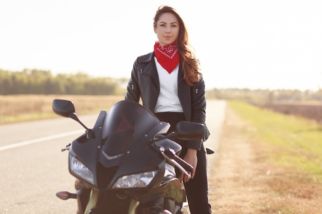 Female motocross racer dressed in black leather jacket, poses on her motorcycle, has adventure in countryside, likes risky sport