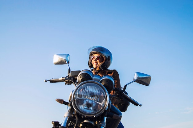 Female motorbike rider wearing helmet and riding retro style motorcycle