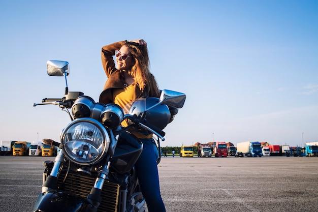 レトロなバイクに座って笑顔の革のジャケットの女性モーターサイクリスト