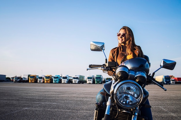Female motorcyclist in leather jacket sitting on retro motorbike and smiling
