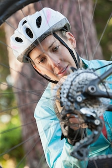 Женский горный велосипедист осматривает колесо своего велосипеда