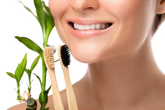 白い歯と竹の歯ブラシを持つ女性の口