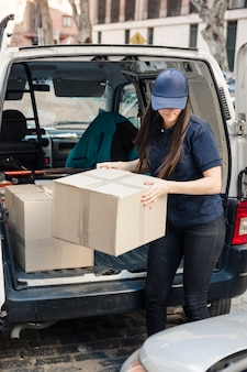 Female mover unloading cardboard boxes from vehicle