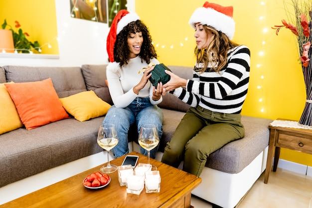 화이트 와인 잔으로 선물을주는 집에서 축하하는 산타 모자와 여성 다중 민족 부부