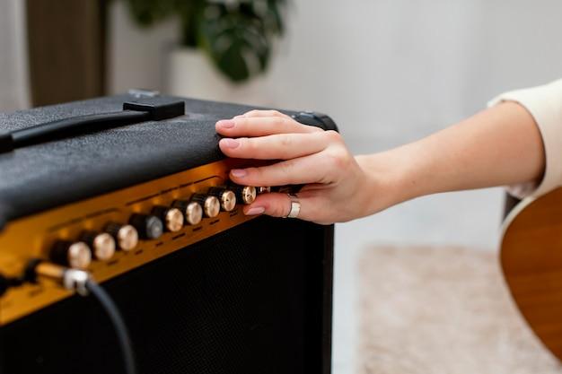 Female musician adjusting amplifier for her guitar