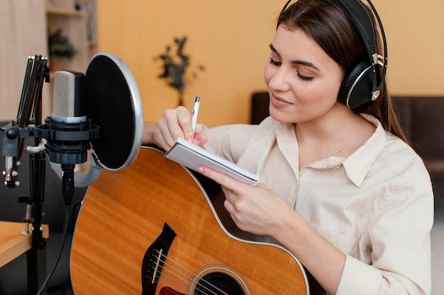 Musicista femminile a casa a scrivere una canzone mentre si suona la chitarra acustica
