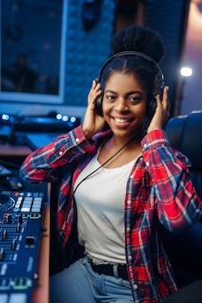 Женский музыкант в наушниках в студии звукозаписи