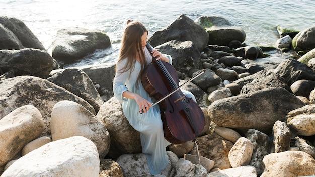 Женский музыкант на скалах играет на виолончели у океана