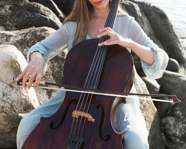 Женский музыкант на скалах играет на виолончели