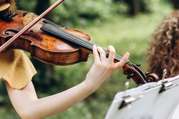 Female musician performs at an outdoor wedding.