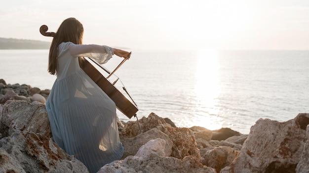 コピースペースのある岩の上で日没時にチェロを演奏する女性ミュージシャン