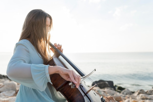 Female musician playing cello by the sea
