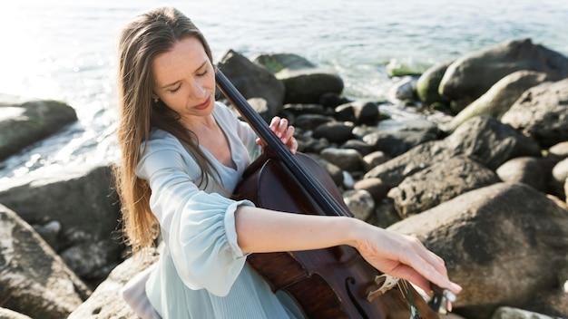 Женский музыкант играет на виолончели у океана