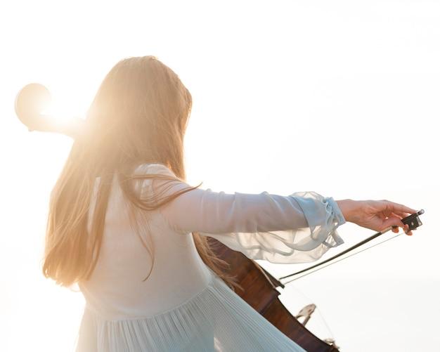 太陽の下でチェロを弾く女性ミュージシャン
