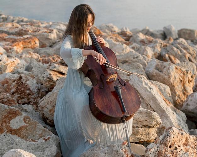 야외에서 바위에 첼로 연주 여성 음악가