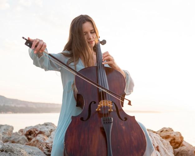 야외에서 첼로 연주 여성 음악가