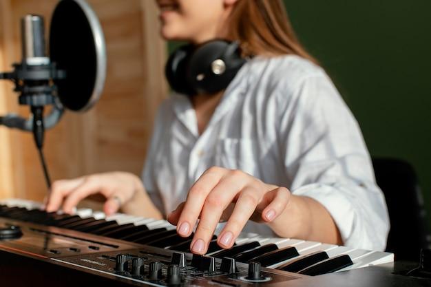 室内でピアノ鍵盤を弾き、歌を録音する女性ミュージシャン