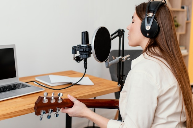 Female musician recording song while playing acoustic guitar at home