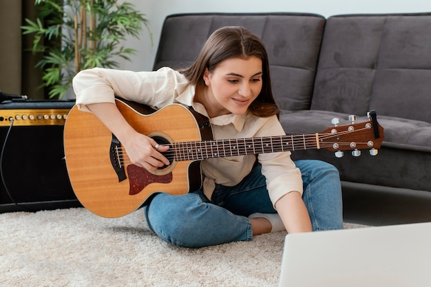 Female musician with acoustic guitar and laptop