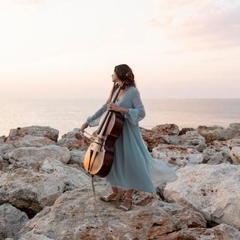 屋外でチェロを持つ女性ミュージシャン