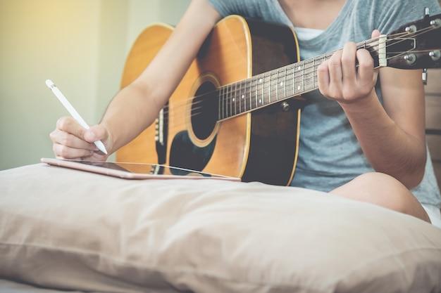 여성 뮤지션은 태블릿을 사용하여 기타를 연주하고 노래를 씁니다.