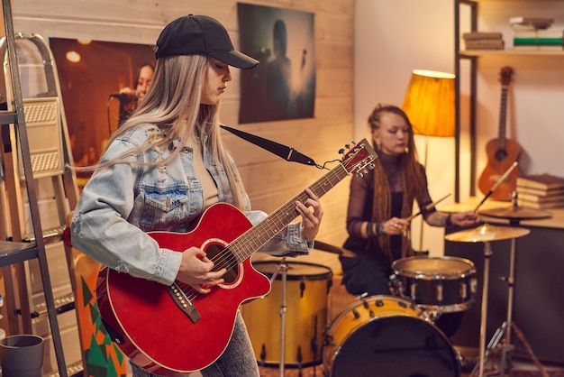 Female musicians playing guitar and drum in modern studio