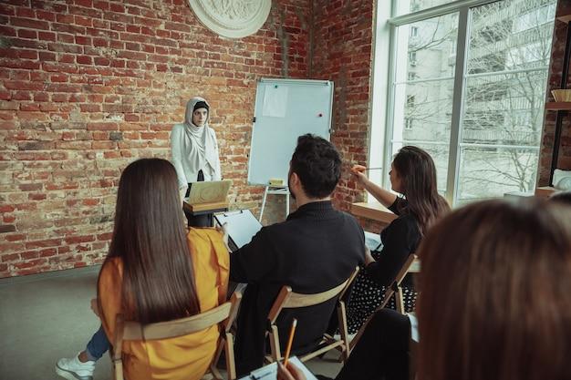 ワークショップのホールでプレゼンテーションを行う女性のイスラム教徒のスピーカー。聴衆または会議ホール。