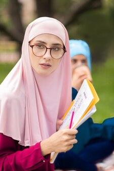 女性のイスラム教徒の学生。外に座って一緒に勉強している明るいヒジャーブを身に着けている女性のイスラム教徒の学生