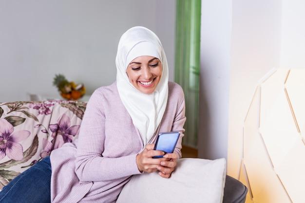 ソファソファに座ってリラックスしているときにモバイル情報を検索するモバイルスマートフォンを使用している女性のイスラム教徒。
