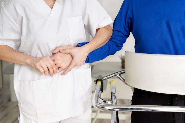 Женщина-медсестра, держащая пациента за руку, поддерживает пациента-инвалида, сидящего на инвалидной коляске в больнице, молодой врач-сиделка помогает парализованному пациенту.