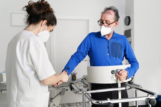 女性看護師の介護者は、患者の手を握り、障害のある患者が病院の車椅子に座るのをサポートし、若い医師の介護者が麻痺した患者を助けます。
