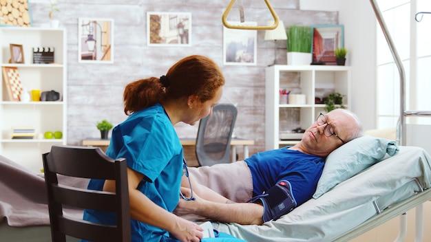 老人病人の血圧をチェックする女性看護師。老人は明るく居心地の良い介護リタイヤメントホームの病院のベッドに横たわっています