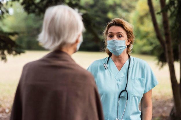 노인 여자와 야외에서 대화하는 여성 간호사