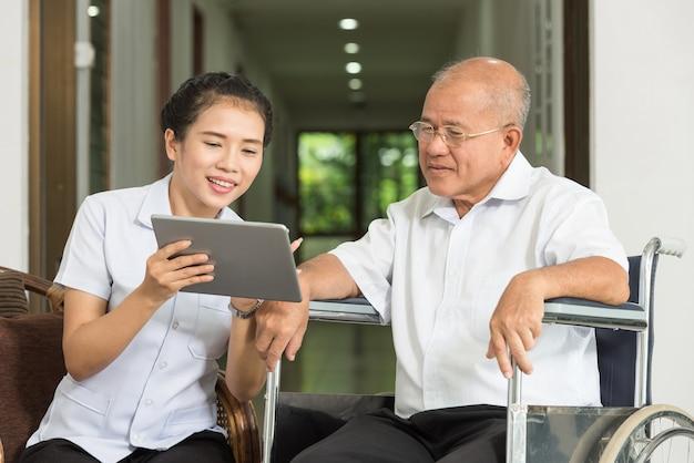 요양원에서 휠체어에 수석 남자와 디지털 태블릿을 통해 논의 여성 간호사