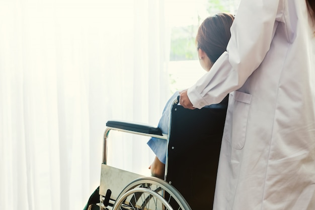 Female nurse or doctor pushing patient on a wheelchair in the hospital for help support