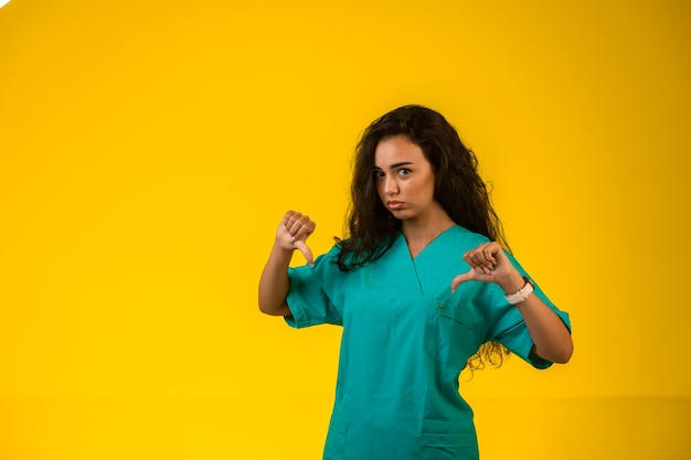 親指を下に向けて失望した顔をしている女性看護師。