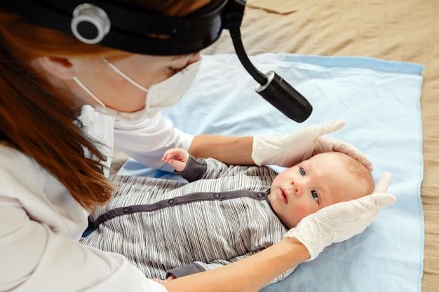 Female nurse examining cute little kid