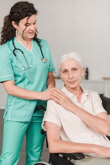 Female nurse giving support to senior woman sitting on wheel chair