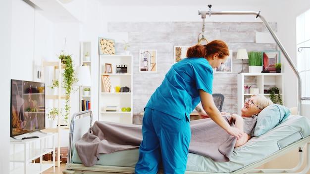大きな窓のある老人ホームで老婦人が就寝するのを手伝い、毛布で覆う女性看護師