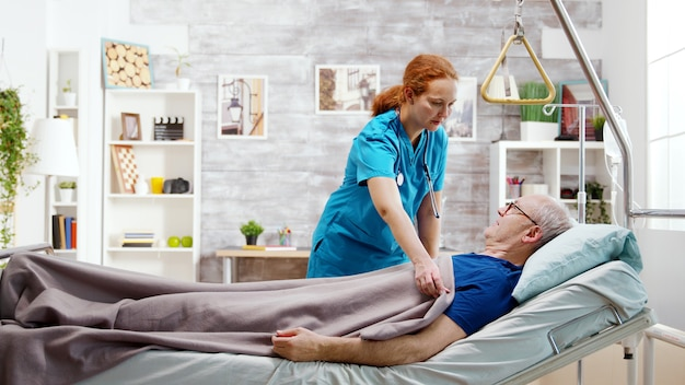 Female nurse helping an old disabled sick man who lies in hospital bed in a nursing retirement home