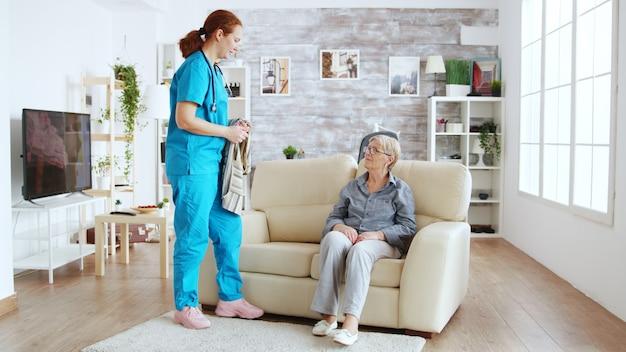 ナーシングホームに着替える年配の女性を助ける女性看護師