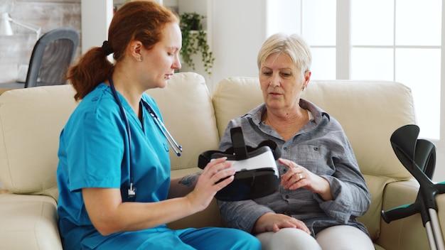 ナーシングホームでvrゴーグルを使って年配の女性がバーチャルリアリティを体験するのを手伝う女性看護師